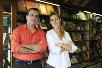 man and woman standing in front of books being displayed on bookshelves